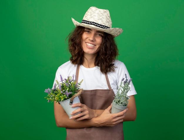 Lächelnder junger weiblicher gärtner in der uniform, die gartenhut hält und blumen in blumentöpfen trägt, die auf grüner wand lokalisiert werden