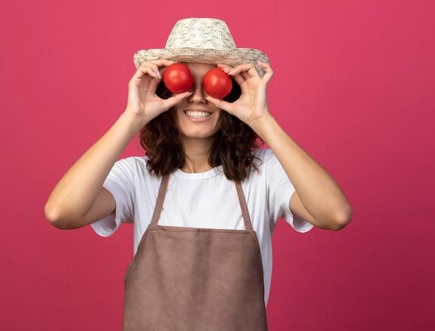 Lächelnder junger weiblicher gärtner in der uniform, die gartenhut trägt, der blickgeste mit tomaten lokalisiert auf rosa zeigt