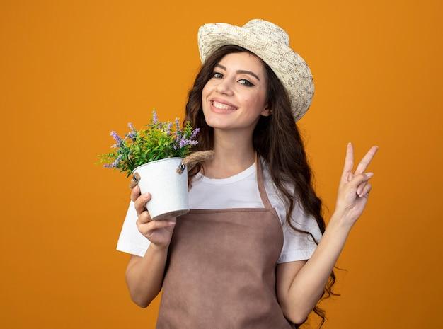 Lächelnder junger weiblicher gärtner in der uniform, die gartenhut trägt, hält blumentopf und gestikuliert siegeshandzeichen lokalisiert auf orange wand mit kopienraum