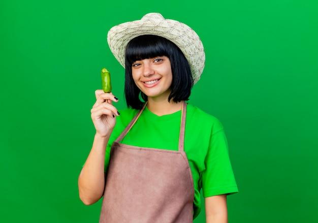 Lächelnder junger weiblicher gärtner in der uniform, die gartenhut trägt, hält gebrochenen pfeffer