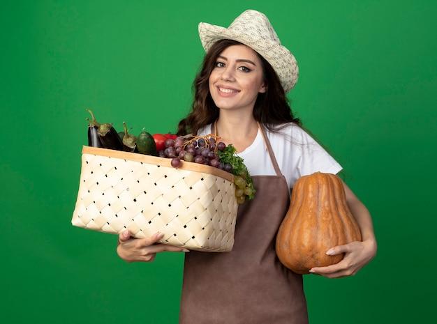 Lächelnder junger weiblicher gärtner in der uniform, die gartenhut trägt, hält gemüsekorb und kürbis lokalisiert auf grüner wand mit kopienraum