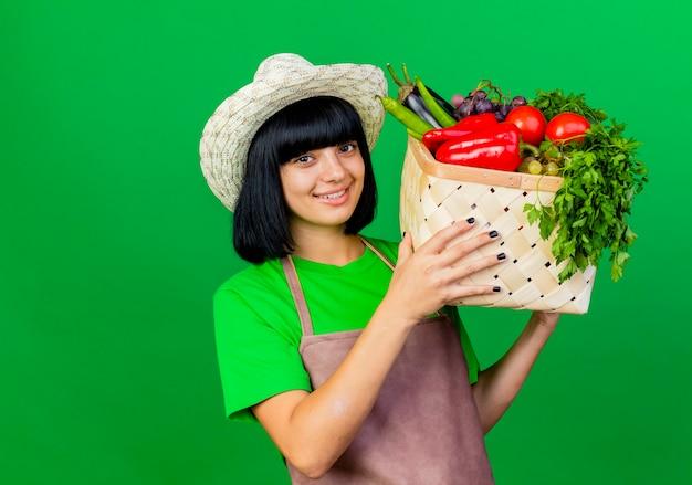 Lächelnder junger weiblicher gärtner in der uniform, die gartenhut trägt, hält gemüsekorb