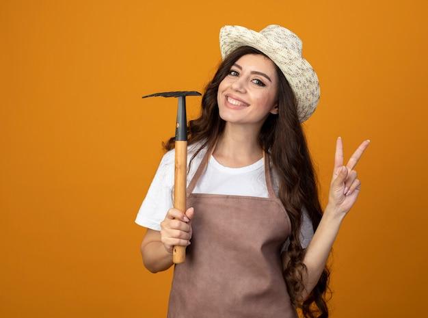 Lächelnder junger weiblicher gärtner in der uniform, die gartenhut trägt, hält rechen und gestikuliert siegeshandzeichen lokalisiert auf orange wand mit kopienraum