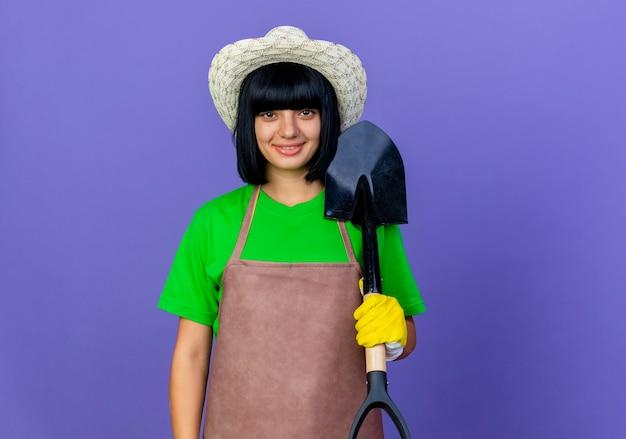 Lächelnder junger weiblicher gärtner in der uniform, die gartenhut und handschuhe trägt, die spaten halten