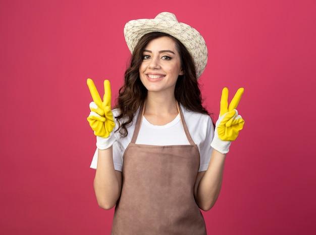 Lächelnder junger weiblicher gärtner in der uniform, die gartenhut und handschuhe trägt, gestikuliert siegeshandzeichen mit zwei händen lokalisiert auf rosa wand mit kopienraum