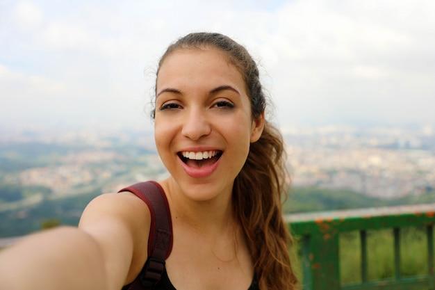 Lächelnder junger weiblicher rucksacktourist machen selbstporträt auf pico do jaragua mit skyline der metropole sao paulo auf dem hintergrund, brasilien