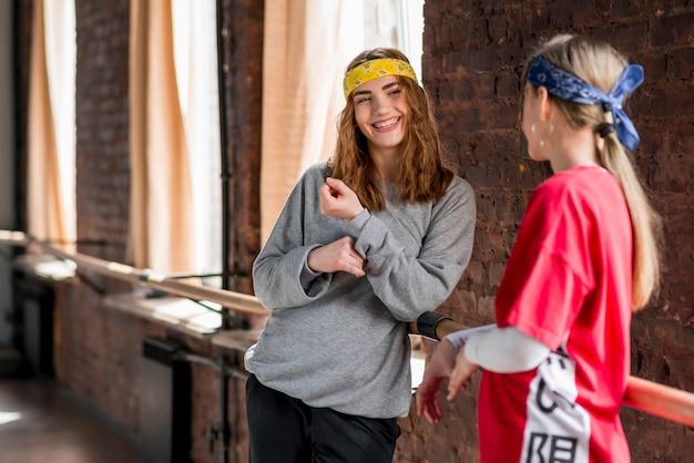 Lächelnder junger weiblicher tänzer, der nahe dem barre im tanzstudio steht