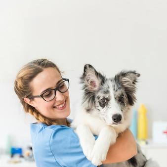 Lächelnder junger weiblicher tierarzt mit hund in der klinik