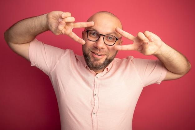 Lächelnder kahler mann mittleren alters, der rosa t-shirt mit brille zeigt, die friedensgeste lokalisiert auf rosa wand zeigt