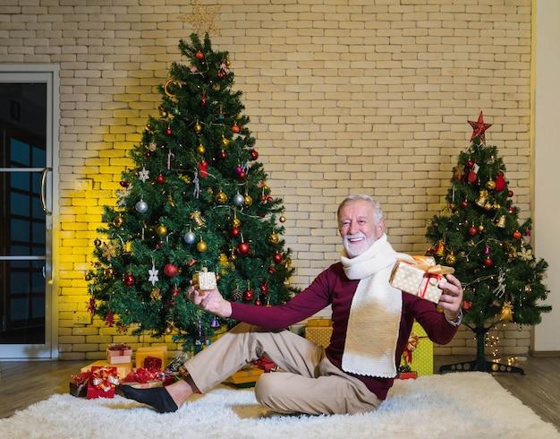 Lächelnder kaukasischer älterer mann, der geschenke auf weißem pelzteppich vor geschmücktem weihnachtsbaum mit glücklichem gesicht mit geschenken im wohnzimmer hält.