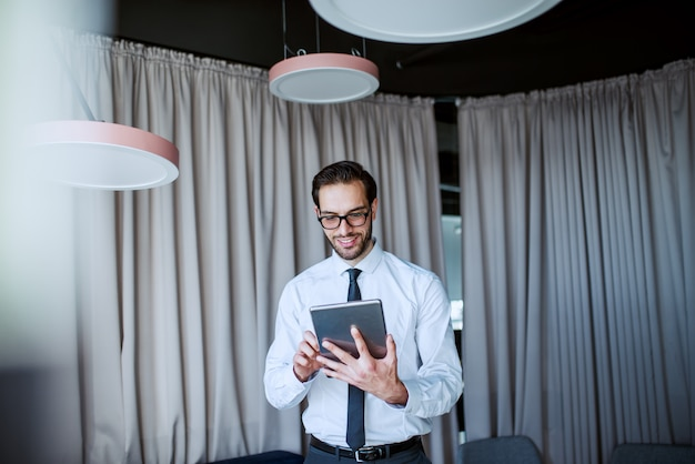 Lächelnder kaukasischer bärtiger geschäftsmann in hemd und krawatte und mit brillen, die im modernen büro stehen und tablette verwenden.