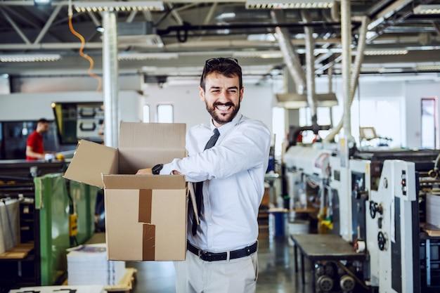 Lächelnder kaukasischer bärtiger grafikingenieur im hemd und in der krawatte, die in druckerei gehen und box verlegen.