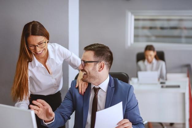 Lächelnder kaukasischer geschäftsmann, der an seinem arbeitsplatz sitzt und mit seiner kollegin spricht. vertrauen sie, weil sie bereit sind, das risiko einzugehen, nicht weil es sicher oder sicher ist.