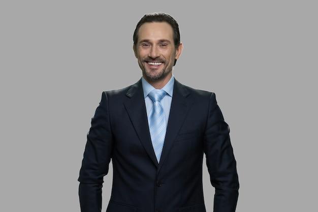 Lächelnder kaukasischer geschäftsmann, der kamera betrachtet. porträt des fröhlichen mannes im geschäftsanzug auf grauem hintergrund.