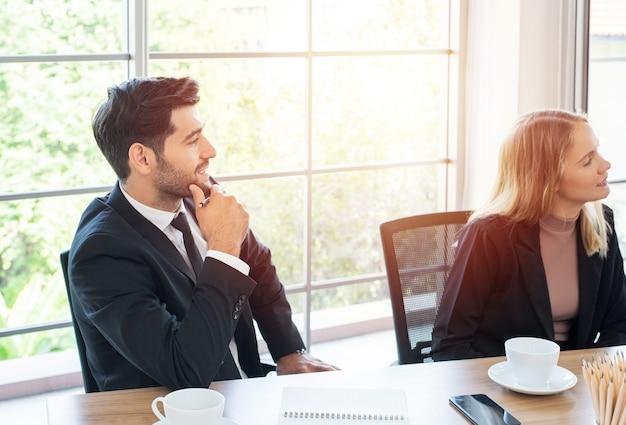 Lächelnder kaukasischer geschäftsmann verschiedene kollegen brainstorming lachen bei bürotreffen