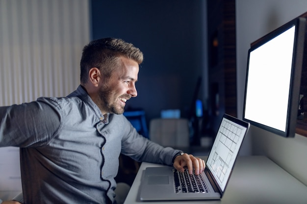 Lächelnder kaukasischer hübscher architekt, der spät in der nacht im büro sitzt und projekt auf laptop beendet.