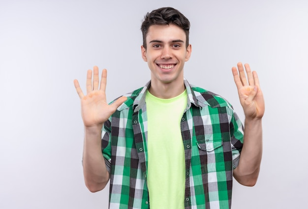 Lächelnder kaukasischer junger mann, der grünes hemd trägt, das fünf und vier mit händen auf lokalisiertem weißem hintergrund zeigt