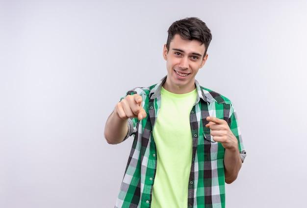 Lächelnder kaukasischer junger mann, der grünes hemd trägt, das sie geste mit beiden händen auf lokalisiertem weißem hintergrund zeigt Kostenlose Fotos