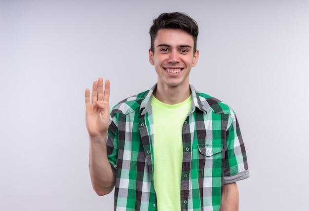 Lächelnder kaukasischer junger mann, der grünes hemd trägt, das vier auf lokalisiertem weißem hintergrund zeigt