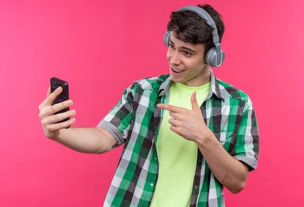 Lächelnder kaukasischer junger mann, der grünes hemd trägt, hören musik auf kopfhörern zeigt telefon auf seiner hand auf lokalisiertem rosa hintergrund