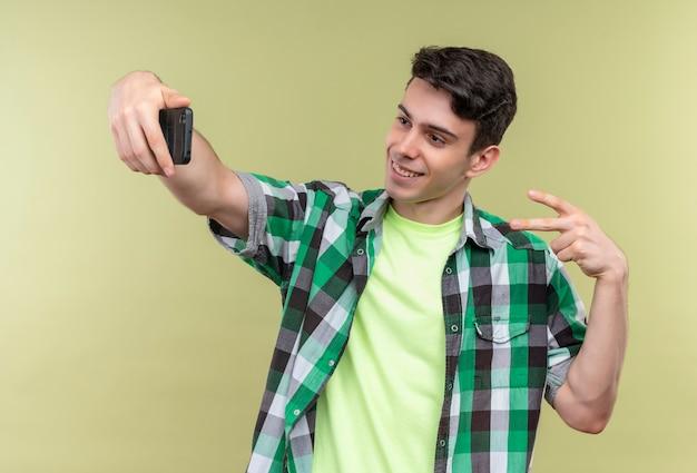 Lächelnder kaukasischer junger mann, der grünes hemd trägt, nimmt selfie, das friedensgeste auf lokalisiertem grünem hintergrund zeigt