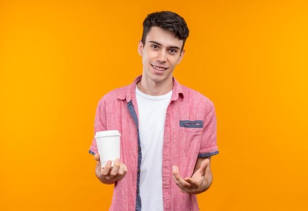 Lächelnder kaukasischer junger mann, der rosa hemd hält, das tasse kaffee hält, hielt hand auf lokalisiertem orangefarbenem hintergrund aus