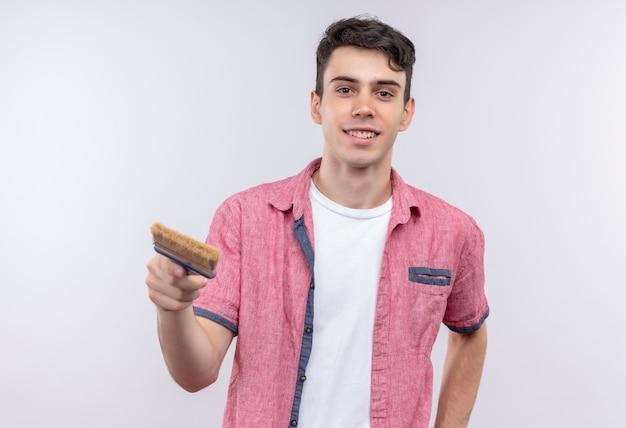 Lächelnder kaukasischer junger mann, der rosa hemd trägt, hielt kamera-pinsel auf lokalem weißem hintergrund aus