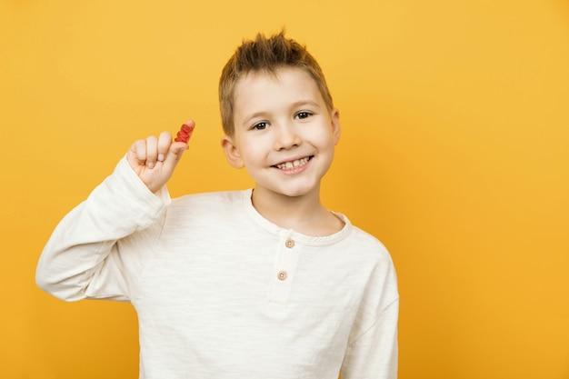 Lächelnder kaukasischer kleinkindjunge, der gummibärchen des gelees in seiner hand hält. isoliert