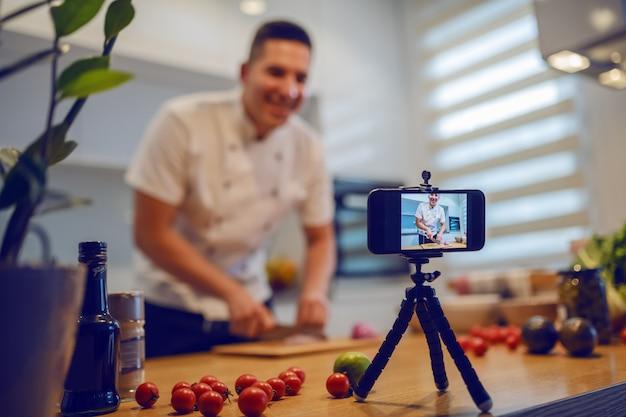 Lächelnder kaukasischer koch in der uniform, die in der küche steht und zwiebel schneidet, während er sich für blog filmt.