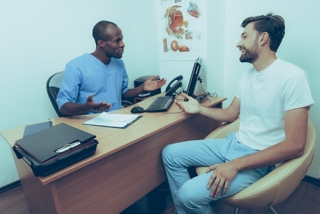 Lächelnder kaukasischer mann bei empfang am doktor
