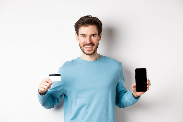 Lächelnder kaukasischer mann, der plastikkreditkarte mit handybildschirm zeigt. kerl, der online-banking-app empfiehlt, auf weißem hintergrund stehend.