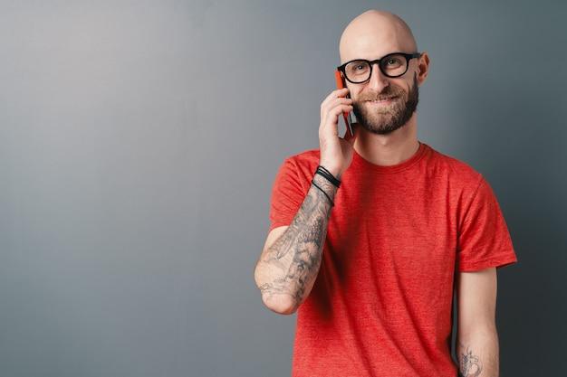Lächelnder kaukasischer mann mit bart, brille, rotem t-shirt, das am telefon über grauem studiohintergrund spricht.