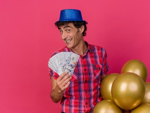 Lächelnder kaukasischer partei-mann mittleren alters, der parteihut hält, der ballons und geld betrachtet kamera betrachtet, die auf purpurrotem hintergrund mit kopienraum lokalisiert wird