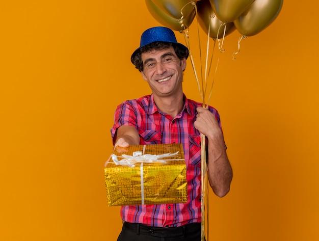 Lächelnder kaukasischer partei-mann mittleren alters, der partyhut hält, der ballons hält kamera betrachtet, die geschenkpackung in richtung kamera lokalisiert auf orange hintergrund mit kopienraum ausdehnt