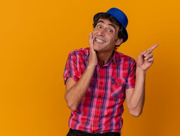 Lächelnder kaukasischer parteimann mittleren alters, der parteihut betrachtet, der kamera berührt, das gesicht zeigt, das auf seite lokalisiert auf orange hintergrund mit kopienraum zeigt