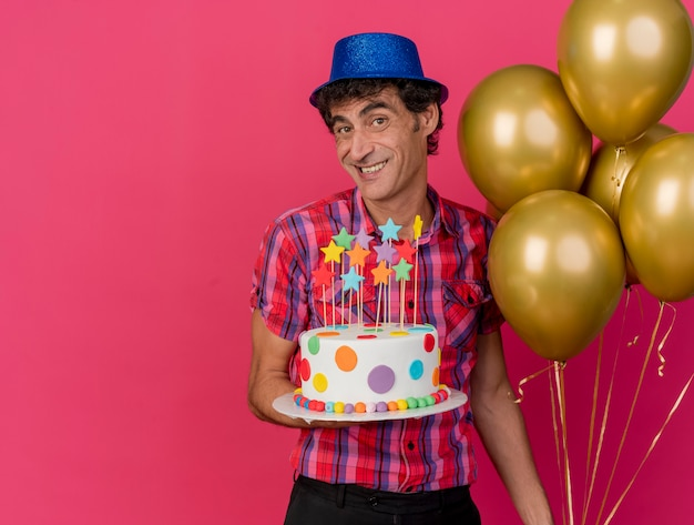 Lächelnder kaukasischer parteimann mittleren alters, der partyhut hält, der ballons und geburtstagstorte hält und kamera lokalisiert auf purpurrotem hintergrund mit kopienraum betrachtet