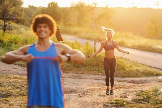 Lächelnder kaukasischer sportlicher mann mit lockigem haar, der dehnungsübungen mit seil in der natur am sonnigen sommertag tut. im hintergrund frau springseil. selektiver fokus auf frau.