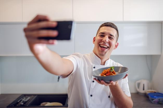 Lächelnder kaukasischer stolzer koch in weißer uniform, die platte mit tagliatelle hält und selfie nimmt, während er in der küche steht.