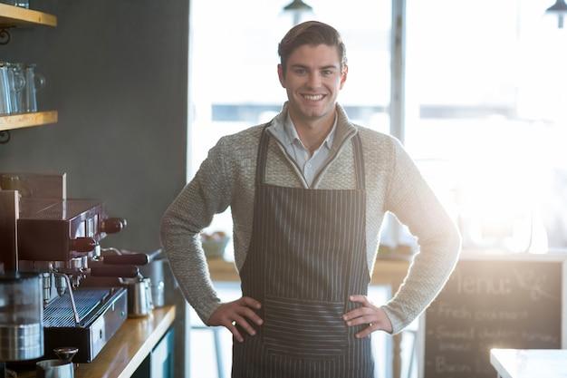 Lächelnder kellner, der mit hand auf hüfte im café steht