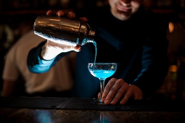Lächelnder kellner, der neues getränk mit blauer flüssigkeit von einem schüttel-apparat in ein glas unter verwendung des siebs gießt