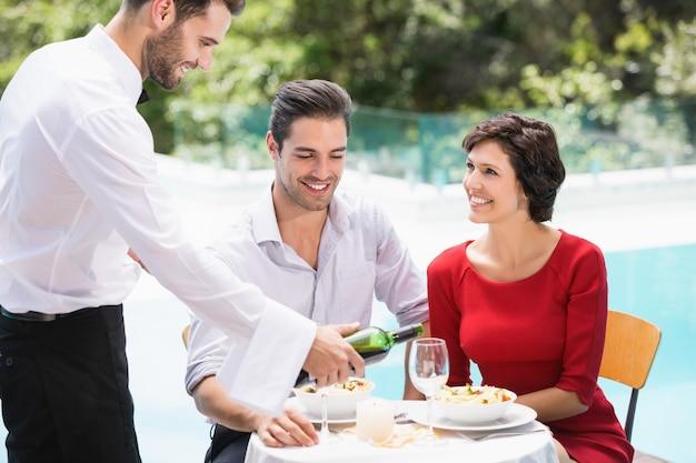 Lächelnder kellner, der rotwein dient, um zu verbinden