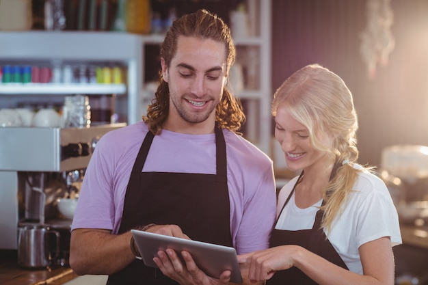 Lächelnder kellner und kellnerin mit digitalem tablet am schalter