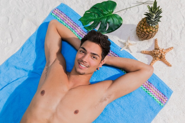 Lächelnder kerl, der auf strand ein sonnenbad nimmt
