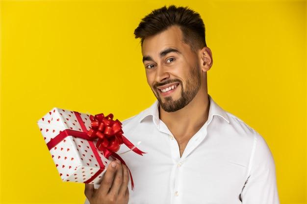Lächelnder kerl, der eine geschenkbox hält