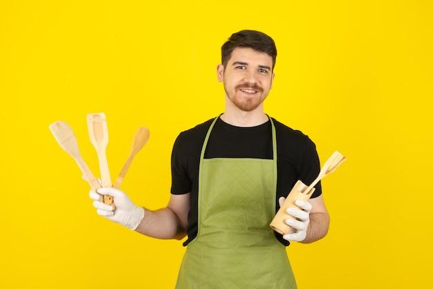 Lächelnder kerl, der hölzerne löffel auf einem gelb hält.