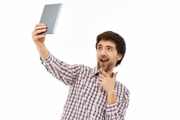 Lächelnder kerl, der selfie nimmt, videoanruf über tablette