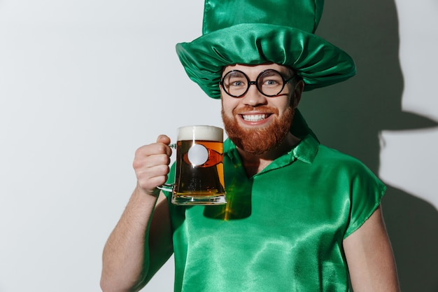 Lächelnder kerl im st.patriks kostüm, das bier hält