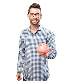Lächelnder kerl mit brille ein sparschwein zeigt
