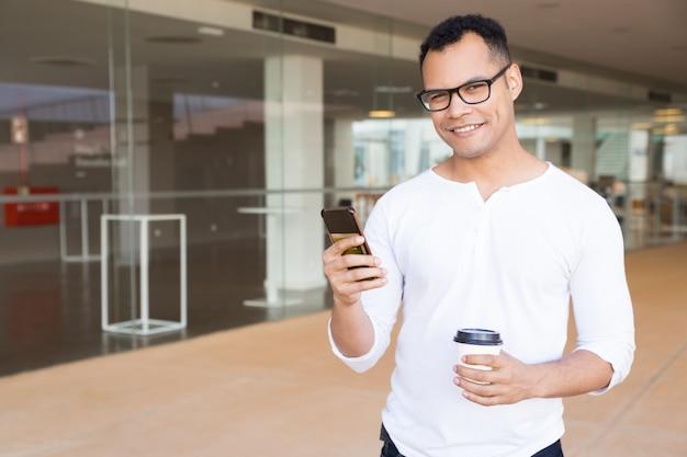 Lächelnder kerl mit dem smartphone, der kamera betrachtet