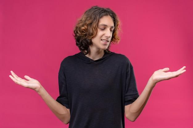 Lächelnder kerl mit langen haaren im schwarzen t-shirt breitete seine hände auf rosa wand aus